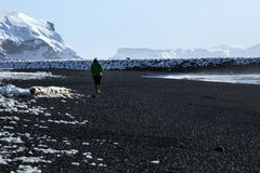 Woman walks along black sand beach in Vik, Iceland Stock Photo
