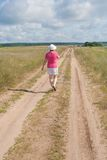 A woman walks along a country road Royalty Free Stock Photos
