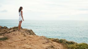 Woman walks along the edge of the cliff and looks at the endless ocean at sunset stock video