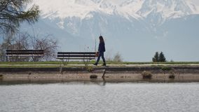 Woman walks along the lake embankment to a bench and sits down to relax and look at a beautiful lake. Swiss Alps are on. The background 4k stock video footage