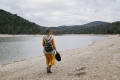 Woman walks along the lake shore Stock Images