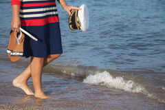 Woman walks along sandy beach with marine cap in hand Stock Image