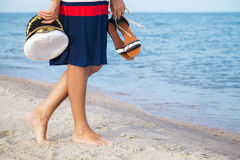 Woman walks along sandy beach with marine cap in hand Royalty Free Stock Images