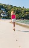 Woman walks along seashore. Focus on footprints Royalty Free Stock Photo