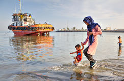 Woman walks along shore of Persian Gulf with her child. Stock Photos