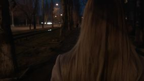 A woman walks along the street at night. A girl on roller skates is going to meet her. We follow the blonde from behind