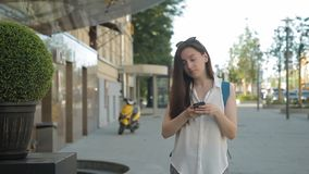 Woman walks around city and searches for sights by phone navigator. Female tourist travels through center and finds architecture through photos on smartphone stock video footage