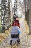 Woman walks in autumn park with baby buggy Stock Photography
