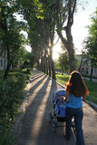 A woman walks with a baby in a stroller. Oman with long hair rolls the stroller. A walk with the baby Stock Photos