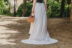 A woman with a white dress walks with a basket full of red apples. royalty free stock photo