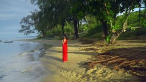 The woman walks on the beach along water. A privacy with the nature. The woman on the tropical island.. On this video you can see as the woman in a red dress stock footage