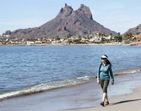 A Woman Walks the Beach, Tetakawi Mountain Behind, San Carlos, M. A Woman Walks the Beach with Tetakawi Mountain Behind, San Carlos, Mexico Royalty Free Stock Image