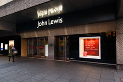 Woman walks by Boxing Day sale POS outside John Lewis department Stock Image