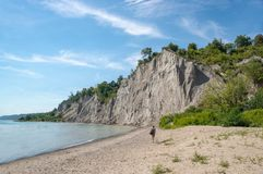 Woman Walks on Brown Seashore Near Cliff With Green Trees Under Blue and White Sky Royalty Free Stock Photography