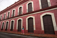 A woman walks in Buga Colombia. July 10, 2017 Buga, Valle de Cauca, Colombia: a woman walks in the front of a colourful colonial building in the historic centre Royalty Free Stock Image