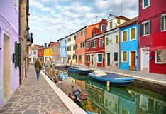Woman walks in Burano island picturesque street with small colored houses in row, water canal with fishermans boats, c royalty free stock image