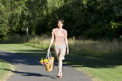 Woman Walks Carrying Flowers - Horizontal Royalty Free Stock Images
