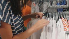 Woman chooses clothes in the store. stock footage
