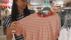 Woman buys new t-shirts for summer. Woman in clothing store looking for new clothes. stock video