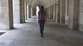 Woman walks through the colonnade of the Gothic cathedral stock video footage