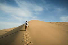 A woman walks through desert sand dunes Stock Photos