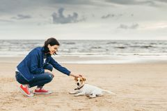 Woman walks with dog on shore Royalty Free Stock Image