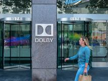 Woman walks by Dolby Laboratories headquarters sign. SAN FRANCISCO, CA August 8, 2018: Woman walks by Dolby Laboratories headquarters sign royalty free stock image