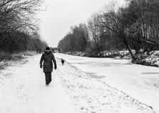 A woman walks down the frozen canal towpath stock images