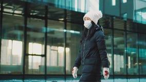 Woman walks in empty street, wears mask at quarantine. Coronavirus epidemic.