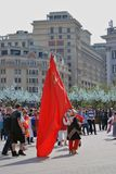 A woman walks holding a red Soviet Union flag. Stock Images