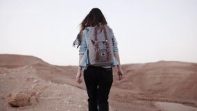 Woman walks near desert canyon. Slow motion. Young woman wanders near sheer drop edge. Rocks and stones. Israel. Freedom. Peaceful summer dusk. Travel and stock video