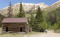 A Woman Walks by an Old Cabin on the Alpine Loop Backcountry Byw. Ay in Colorado Stock Photo