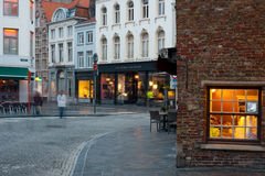 Woman walks by old street of Bruges Stock Image