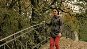 A woman walks in the park, going through the old bridge, sunny autumn day. A woman walks in the park, going through the old bridge stock video