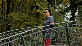 A woman walks in the park, going through the old bridge, sunny autumn day. A woman walks in the park, going through the old bridge stock video footage