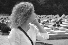 A woman walks past a multitude of graves in the cemetery, black and white photo stock photo