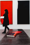 A woman walks past some books laid out with color coordinated ba Stock Photo