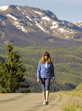 A Woman Walks a Paved Section of the Alpine Loop Backcountry Byw. A Woman Walks a Rare Paved Section of the Alpine Loop Backcountry Byway in Colorado Royalty Free Stock Image