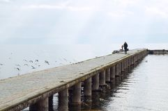 Woman walks on the pier of Ohrid lake, blurred. OHRID, MACEDONIA - MARCH 12, 2017: Woman walks on the pier of Ohrid lake, purposely blurred, selective focus on Stock Photography