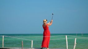 The woman walks on a pier with Selfie stick. Slow mothion. The woman in a long red dress is photographed on the. On this video you can see as the woman in a red stock footage