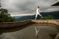 Woman walks by pool in mountain during cloudy day Royalty Free Stock Photos