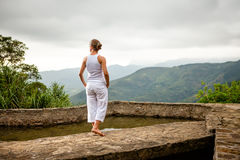 Woman walks by pool in mountain during cloudy day Stock Photography