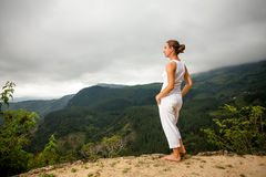 Woman walks by pool in mountain during cloudy day Stock Photo