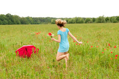 Woman walks through a poppy field Royalty Free Stock Images