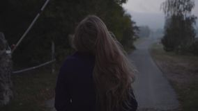 A woman walks on the road and looks at the sky against the background of the village and the barrier. Long-haired woman walks on the road and looks at the sky stock footage