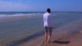 Woman walks at sea water on sandy beach off-season wears in hoodie and hat. stock footage
