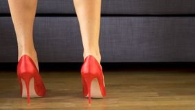 Woman walks sensually in red high heels showing and slim long legs. On the wooden floor stock footage