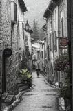 Woman walks by in a street of the medieval French village of Saint-Guilhem-le-Désert royalty free stock image