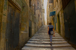 A woman walks through the street of Valletta. Stock Images