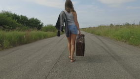 Woman walks with a suitcase on the road stock video footage